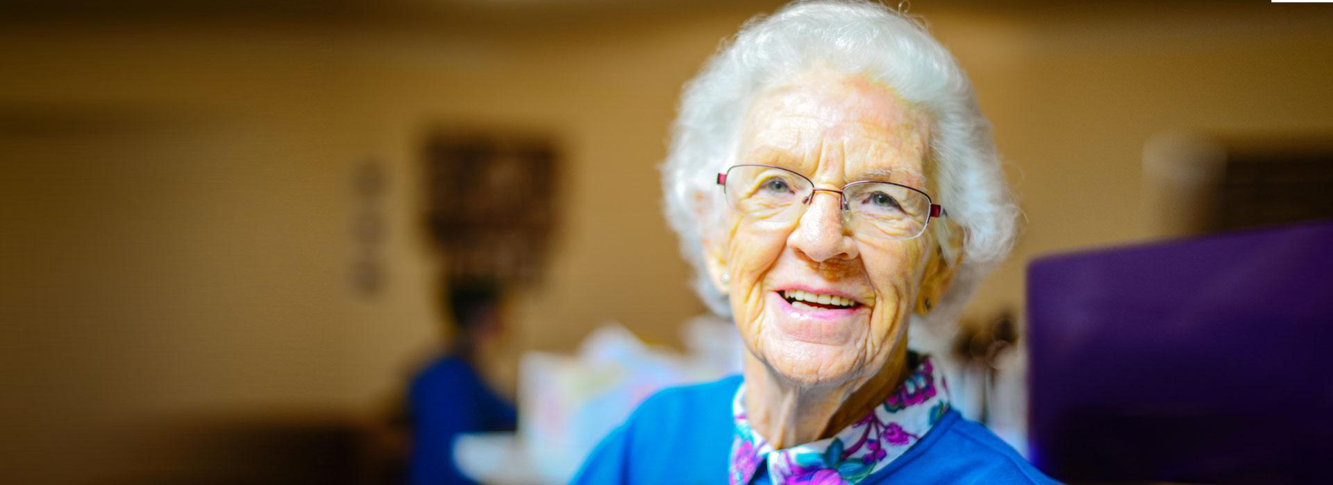 Glückliche Alte Frau in der Pflege